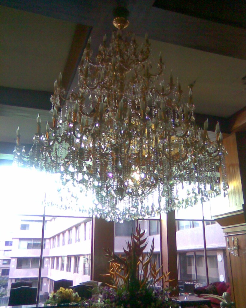huge chandelier looming on glass finished table